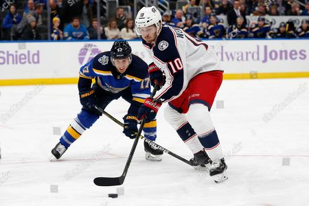 Columbus Blue Jackets' Alexander Wennberg (10), of Sweden, and St. Louis Blues' Jaden Schwartz (17) chase the puck during the first period of an NHL hockey game, in St. Louis