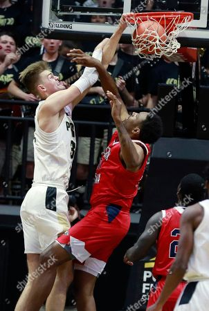 Purdue center Matt Haarms, left, dunks over Southern Indiana forward Josh Price during an exhibition NCAA college basketball game, in West Lafayette, Ind