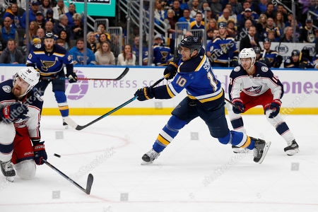 St. Louis Blues' Brayden Schenn, center, scores past Columbus Blue Jackets' David Savard, left, and Alexander Wennberg, right, during the second period of an NHL hockey game, in St. Louis