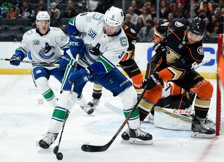 Vancouver Canucks center J.T. Miller, left, handles the puck while pressured by Anaheim Ducks defenseman Michael Del Zotto during the first period of an NHL hockey game in Anaheim, Calif