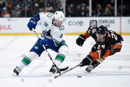 Anaheim Ducks right wing Carter Rowney, right, reaches for the puck handled by Vancouver Canucks center J.T. Miller during the first period of an NHL hockey game in Anaheim, Calif
