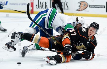 Stock Picture of Anaheim Ducks center Rickard Rakell, front, falls to the ice while defended by Vancouver Canucks center J.T. Miller, resulting in a holding penalty during the second period of an NHL hockey game in Anaheim, Calif