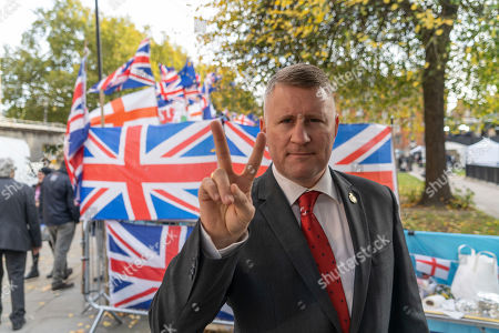 Paul Golding the leader of Britain First gestures outside the House of Parliament.