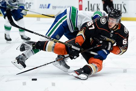 Stock Image of Rickard Rakell, J.T. Miller. Anaheim Ducks center Rickard Rakell, front, falls to the ice while defended by Vancouver Canucks center J.T. Miller resulting in a holding penalty during the second period of an NHL hockey game in Anaheim, Calif