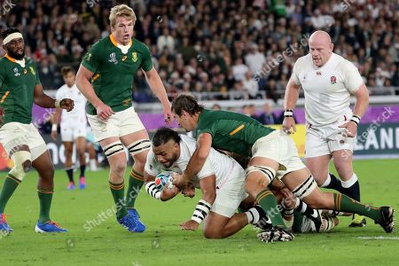 England's Billy Vunipola, center, is tackled by South Africa's Eben Etzebeth during the Rugby World Cup final at International Yokohama Stadium in Yokohama, Japan