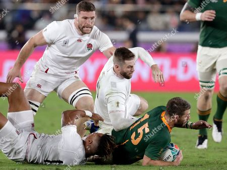 South Africa's Willie Le Roux, right, is brought down by England's Anthony Watson, and Elliot Daly, center, during the Rugby World Cup final at International Yokohama Stadium between England and South Africa in Yokohama, Japan