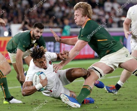England's Anthony Watson, center, is covered by South Africa's Pieter-Steph du Toit, right, during the Rugby World Cup final at International Yokohama Stadium between England and South Africa in Yokohama, Japan