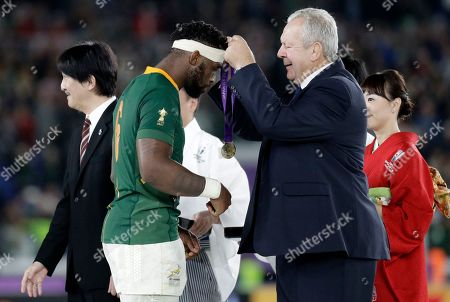 Stock Picture of World Rugby chairman Bill Beaumont, right, presents the winners medal to South Africa's Siya Kolisi after they defeated England in the Rugby World Cup final at International Yokohama Stadium in Yokohama, Japan