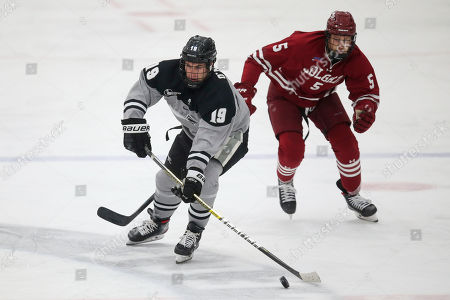 Providence's Jason O'Neill (19) skates with the puck as Colgate's Paul McAvoy (5) follows on the play during an NCAA hockey game on in Providence, R.I