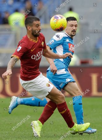 Roma's Javier Pastore, left, and Napoli's Mario Rui vie for the ball during an Italian Serie A soccer match between Roma and Napoli, at the Olympic stadium in Rome