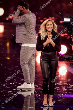 Florian Silbereisen (L) reacts as German singer Helene Fischer (R) performs during the TV show 'Schlagerbooom 2019 - Alles funkelt! Alles glitzert!' (lit.: Hit Booom 2019 - everything sparkles, everything glitters) at the Westfalenhalle in Dortmund, Germany, 02 November 2019.