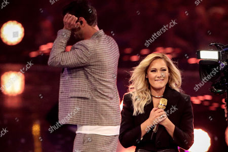 Florian Silbereisen (L) reacts as German singer Helene Fischer (R) performs during the TV show 'Schlagerbooom 2019 - Alles funkelt! Alles glitzert!' (lit.: Hit Booom 2019 - everything sparkles, everything glitters) at the Westfalenhalle in Dortmund, Germany, 02 November 2019.