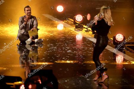 Florian Silbereisen (L) watches German singer Helene Fischer (R) performing during the TV show 'Schlagerbooom 2019 - Alles funkelt! Alles glitzert!' (lit.: Hit Booom 2019 - everything sparkles, everything glitters) at the Westfalenhalle in Dortmund, Germany, 02 November 2019.