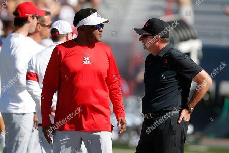 Arizona head coach Kevin Sumlin, left, and Oregon State head coach Jonathan Smith talk before an NCAA college football game, in Tucson, Ariz