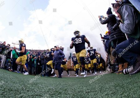 Notre Dame players enter the field led by Notre Dame head coach Brian Kelly during NCAA football game action between the Virginia Tech Hokies and the Notre Dame Fighting Irish at Notre Dame Stadium in South Bend, Indiana