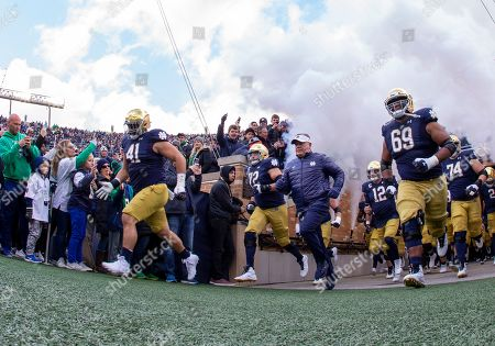 Notre Dame players enter the field led by Notre Dame head coach Brian Kelly during NCAA football game action between the Virginia Tech Hokies and the Notre Dame Fighting Irish at Notre Dame Stadium in South Bend, Indiana. Notre Dame defeated Virginia Tech 21-20