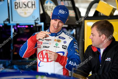 Joey Logano talks with a team member in the garage during a NASCAR Cup Series auto race practice at Texas Motor Speedway in Fort Worth, Texas