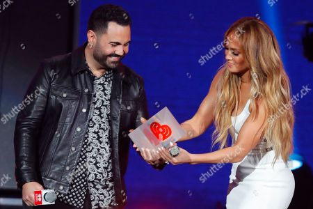 Jennifer Lopez, Enrique Santos. Host Enrique Santos presents Jennifer Lopez with the iHeartRadio Premio Corazon Award at the 2019 iHeartRadio Fiesta Latina, in Miami