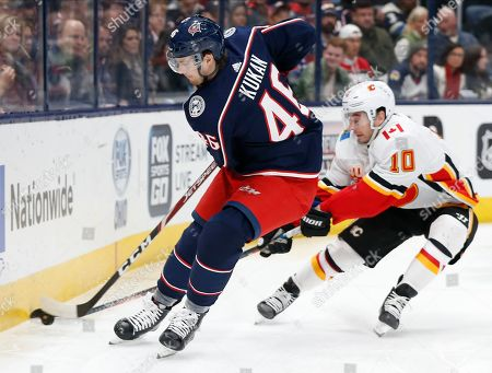 Columbus Blue Jackets' Dean Kukan, left, of Switzerland, tries to clear the puck as Calgary Flames' Derek Ryan defends during the first period of an NHL hockey game, in Columbus, Ohio