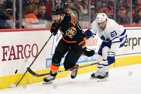 Philadelphia Flyers' Jakub Voracek, left, skates with the puck past Toronto Maple Leafs' Cody Ceci during the second period of an NHL hockey game, in Philadelphia