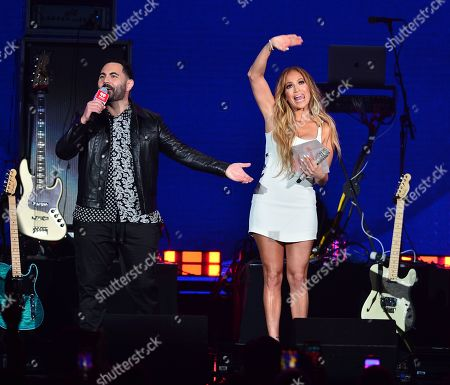 Jennifer Lopez and host Enrique Santos (L) present Jennifer Lopez with the iHeartRadio Premio Corazon Award