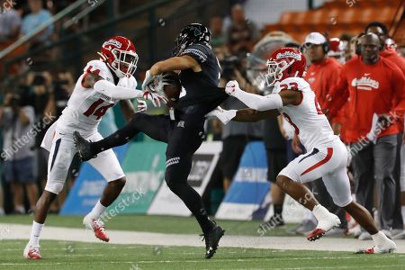 Hawaii wide receiver Jason-Matthew Sharsh (3) gets pulled down by Fresno State defensive backs Jaron Bryant (14) and Juju Hughes (23) during the first half of an NCAA college football game, in Honolulu