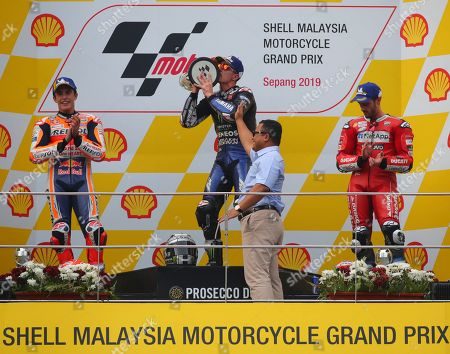 Stock Image of Winner Spanish MotoGP rider Maverick Vinales Ruiz of Monster Energy Yamaha MotoGP team (C-back) celebrates as second-place winner Spanish MotoGP rider Marc Marquez of Repsol Honda Team (L) and third-place winner Italian MotoGP rider Andrea Dovizioso of Ducati team (R) stand on podium during the awards ceremony of the Motorcycling Grand Prix of Malaysia 2019 in Sepang International Circuit, outside Kuala Lumpur, Malaysia, 03 November 2019.