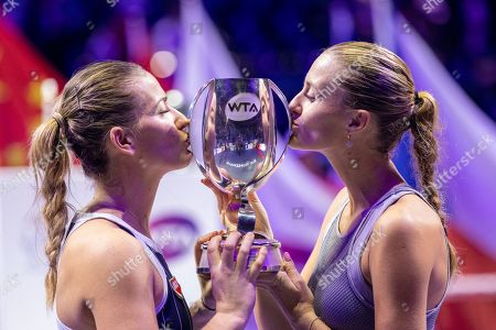 Stock Photo of Timea Babos of Hungary (L) and Kristina Mladenovic of France (R) receive their trophy after winning the women's doubles final match against  Su Wei Hsieh of Chinese Taipei and Barbora Strycova of Czech Republic at the WTA Finales 2019 tournament doubles finales match in Shenzhen, China, 03 November 2019.
