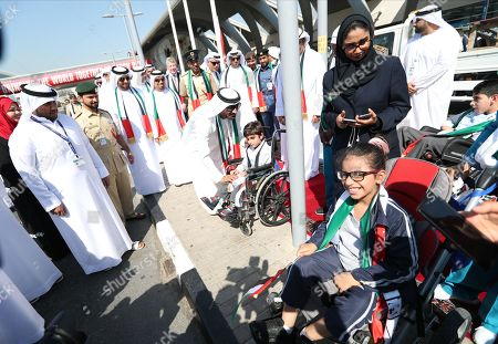 His Highness Sheikh Ahmed Bin Saeed Al Maktoum (C), President of Dubai Civil Aviation Authority, Chairman of Dubai Airports and Chairman and Chief Executive of Emirates Airline and Group, talks to children from people with special needs during celebration of UAE Flag Day in front of Dubai International Airport in Gulf emirate of Dubai, United Arab Emirates, 03 November 2019. The Flag Day is marked to celebrate the national unity for the seven emirates in 1971. It marks the day when Sheikh Khalifa bin Zayed Al Nahyan was elected as the new President of the United Arab Emirates on 03 November 2004 after the death of his father, Sheikh Zayed.