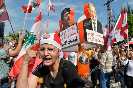 A supporter of the Free Patriotic Movement and President Michel Aoun drags pictures of President Michel Aoun and an orange blood bag that symbolizes the party color during a demonstration to support the President at the entrance of the Lebanese Presidential Palace, east of Beirut, Lebanon, 03 November 2019. The demonstration to express support for the President, caretaker Foreign Minister and leader of Free Patriotic Movement (FPM) Gebran Bassil.
