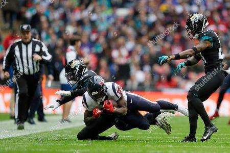 Jacksonville Jaguars defensive back Cody Davis (22) hits Houston Texans running back Duke Johnson (25) during the first half of an NFL football game at Wembley Stadium, in London