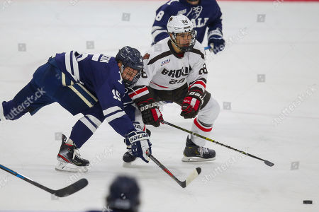 Yale's Kyle Johnson (15) and Brown's Colin Burston (28) battle for the puck during an NCAA hockey game on in Providence, R.I