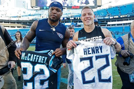 Tennessee Titans running back Derrick Henry, left, and Carolina Panthers running back Christian McCaffrey trade jerseys following an NFL football game in Charlotte, N.C