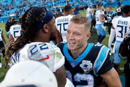 Tennessee Titans running back Derrick Henry (22) and Carolina Panthers running back Christian McCaffrey speak following an NFL football game in Charlotte, N.C