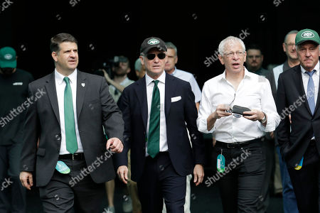 New York Jets owner Woody Johnson, center walks out onto the field during practice before an NFL football game, in Miami Gardens, Fla