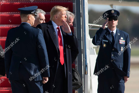 President Donald Trump looks back to the press as he departs Air Force One with Rep. Peter King, R-N.Y., center left, and Rep. Mark Meadows, R-N.C., center right,, at Andrews Air Force Base, after a trip to New York City to attend a mixed martial arts fight at Madison Square Garden