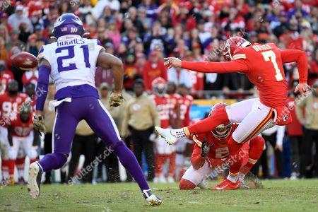 Kansas City Chiefs kicker Harrison Butker (7) boots a winning field goal as Minnesota Vikings cornerback Mike Hughes (21) watches during the second half of an NFL football game in Kansas City, Mo