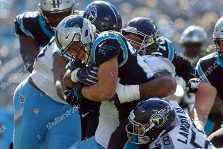 Tennessee Titans defensive end DaQuan Jones, right, and defensive tackle Jeffery Simmons tackle Carolina Panthers running back Christian McCaffrey during the first half of an NFL football game in Charlotte, N.C