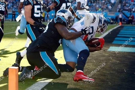 Tennessee Titans running back Derrick Henry (22) scores while Carolina Panthers defensive tackle Dontari Poe (95) tackles during the second half of an NFL football game in Charlotte, N.C