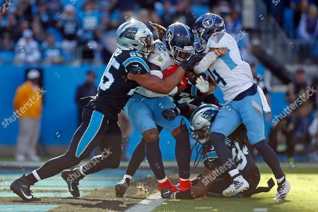 Tennessee Titans running back Derrick Henry (22) scores a touchdopwn while Carolina Panthers strong safety Eric Reid (25) tries to stop the runner while Titans wide receiver Kalif Raymond (14) pushes during the second half of an NFL football game in Charlotte, N.C