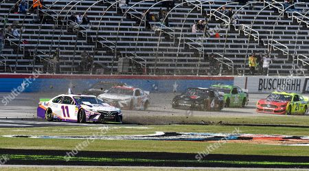 Denny Hamlin (11) wrecks into the grass on the front stretch during a NASCAR auto race at Texas Motor Speedway, in Fort Worth, Texas