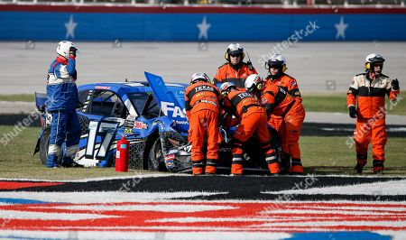Safety personal secure Ricky Stenhouse Jr.'s car after a wreck exiting Turn 4 and ending in the grass on the front stretch during a NASCAR auto race at Texas Motor Speedway, in Fort Worth, Texas