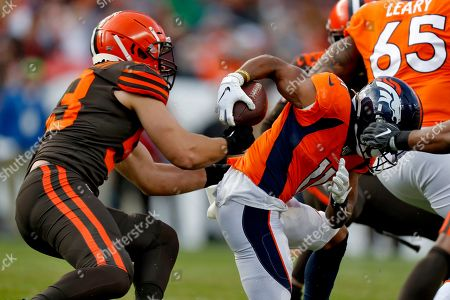 Cleveland Browns middle linebacker Joe Schobert strips the ball from Denver Broncos wide receiver Diontae Spencer (11) during the first half of NFL football game, in Denver. The Browns recovered the ball