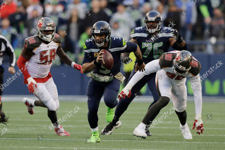 Seattle Seahawks quarterback Russell Wilson (3) scrambles away from Tampa Bay Buccaneers defensive end Jason Pierre-Paul (90) during overtime of an NFL football game, in Seattle
