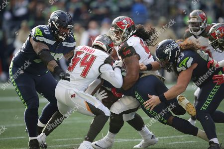 Tampa Bay Buccaneers outside linebacker Lavonte David (54) and defensive tackle Vita Vea, center, wrap up Seattle Seahawks running back Chris Carson (center, obscured) as Seahawks' Mike Iupati, left, and Joey Hunt, right, look on during the first half of an NFL football game, in Seattle