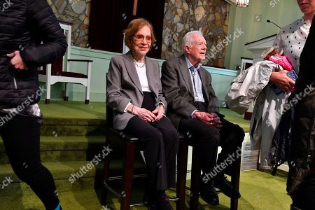 Former U.S. President Jimmy Carter and former first lady Rosalynn Carter, left, sit as guests of Maranatha Baptist Church come and go to have their photo made with them, after Jimmy taught Sunday school there, in Plains, Ga