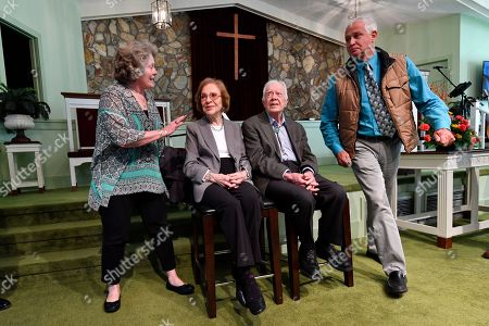 Former U.S. President Jimmy Carter, second from right, and former first lady Rosalynn Carter sit as admiring guests Romona Kluth, left, and husband Doug Kluth, both from Nebraska, finish their turn of having their photo made with them, after Jimmy taught Sunday school at Maranatha Baptist Church, in Plains, Ga