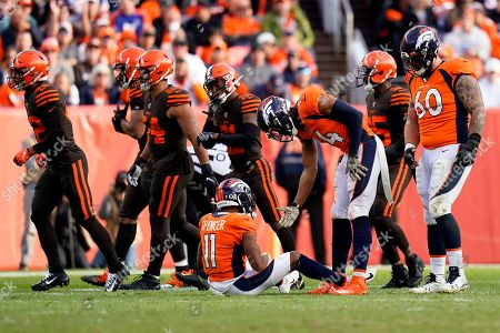 Denver Broncos wide receiver Diontae Spencer (11) is helped up by teammate Courtland Sutton (14) after fumbling the football against the Cleveland Browns during the first half of NFL football game, in Denver. The Browns recovered the ball