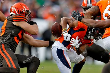 Cleveland Browns middle linebacker Joe Schobert, left, strips the ball from Denver Broncos wide receiver Diontae Spencer during the first half of NFL football game, in Denver. The Browns recovered the football