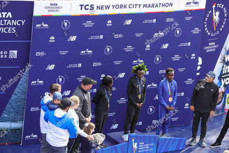 Mary Keitany of Kenya, Joyciline Jepkosgei of Kenya, and Ruti Aga of Kenya pose with the trophy after taking the top three spots in the Women's Division